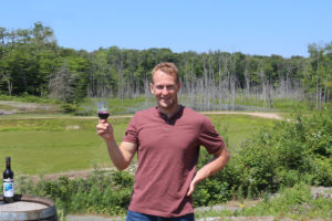 man holding up glass of wine on blueberry hill