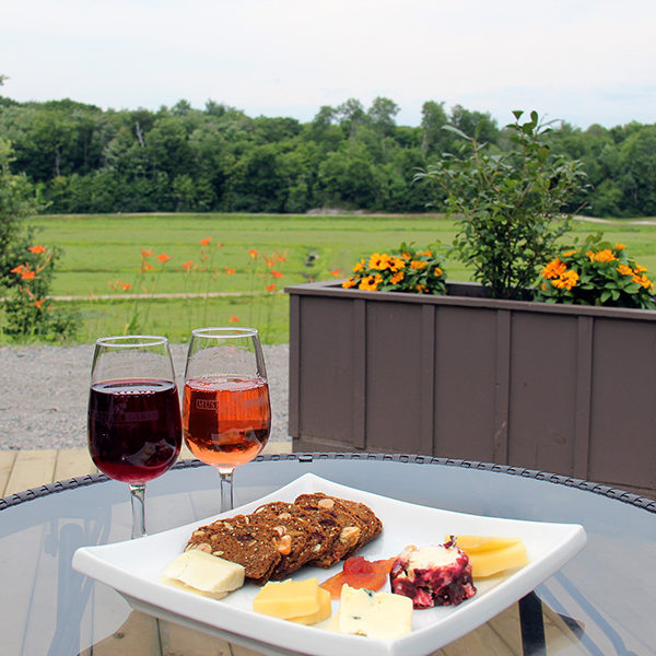two glasses of wine beside a cheese plate on an outdoor patio table