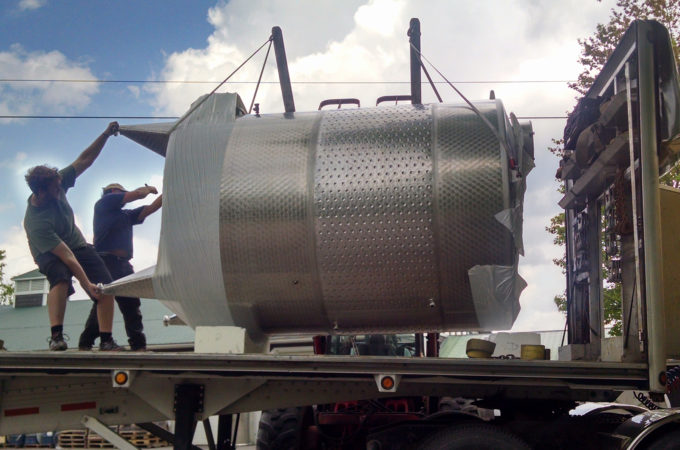 two men guide a large wine tank off a truck