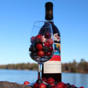 bottle of muskoka lakes cranberry blueberry wine with glass full of cranberries and blueberries