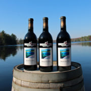 three bottles of muskoka red wine on a barrel with lake in background