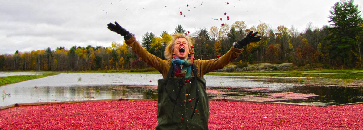 woman standing in johnston's cranberries enthusiasticallyl tossing them into the air