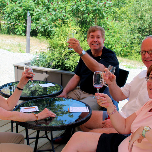 two couples holding up wine glasses sitting on muskoka lakes winery's patio