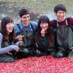 two young couples smiling while crouching in cranberries on a flooded cranberry bed