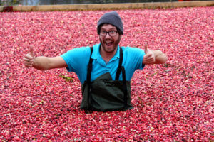 man in flooded cranberries with thumbs up