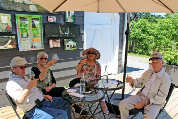 two older couples sampling muskoka lakes wine on the patio