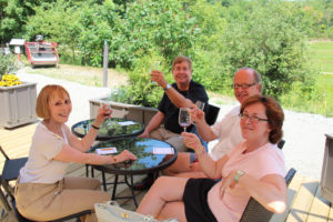 two couples on an outdoor patio sampling wine