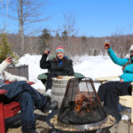 three girls raising wine glasses sitting outside on muskoka chairs around a fire in winter