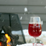 glass of wine outside on the arm of a muskoka chair in front of a fire as snow falls
