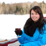 girl holding a glass of wine sitting outside on a muskoka chair with a cheese plate in winter