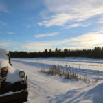 snow covered antique truck beside an open marsh