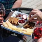 people sampling a plate of cheese, crackers, preserves while holding wine