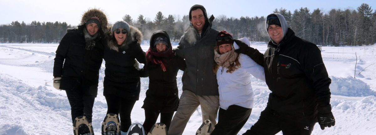 six people with arms linked raising one snowshoed foot against a winter background