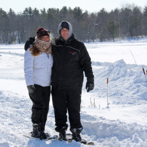 couple in snowshoes with arms around each other on a sunny winter day