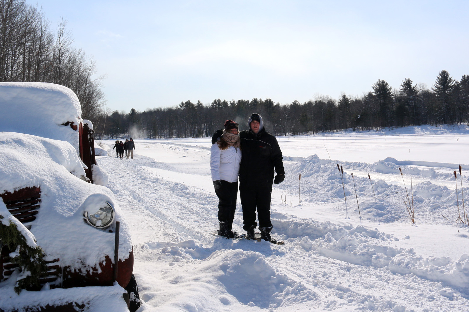 couple standing in snowshoes on a trail beside an old truck on a sunny winter day