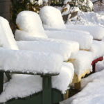 three muskoka chairs covered in snow on a sunny winter day