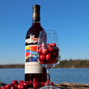 bottle of cranberry wine beside wine glass full of cranberries on granite with lake background