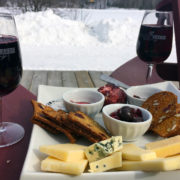 cheese plate with two glasses of muskoka lakes wine on the arm of Muskoka chairs against a snowy background