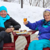 two women in Muskoka chairs enjoying wine and cheese on a winter day