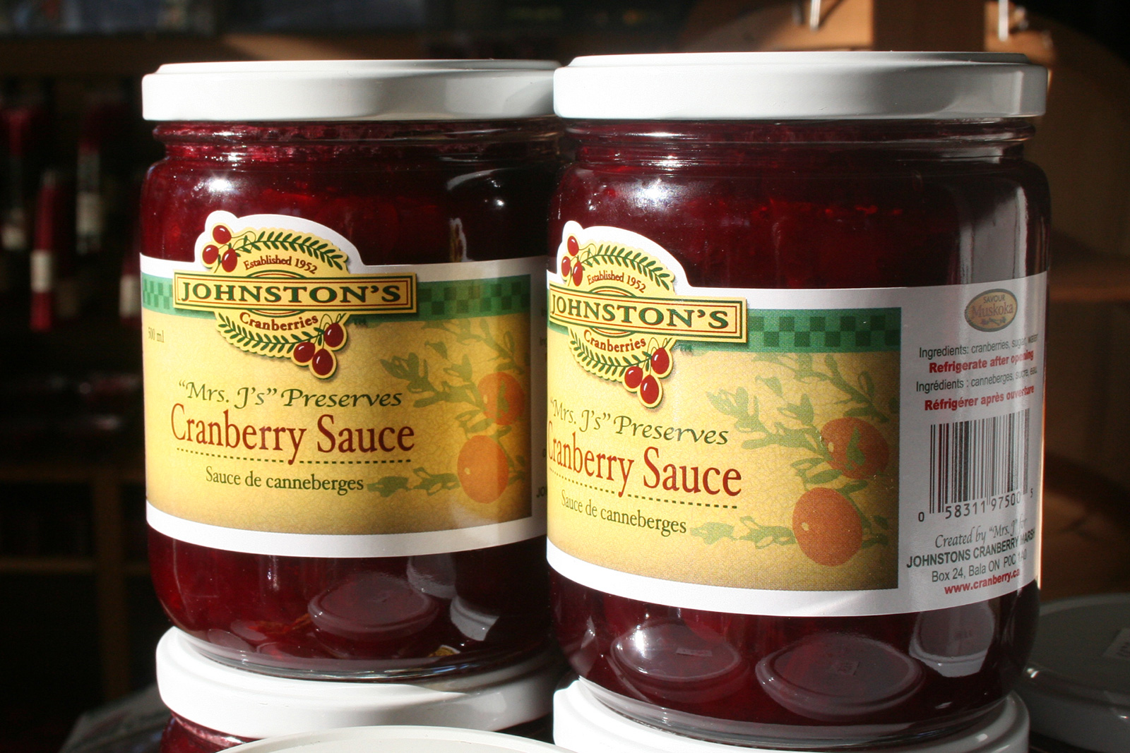 two jars of Mrs. J's cranberry sauce in sunshine