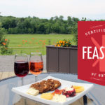 picture of wine & cheese on outdoor table with Feast ON certified logo