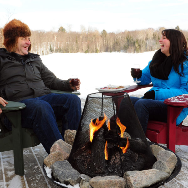 couple laughing and enjoying wine on an outdoor patio in front of a fire in winter time