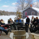 group of people dressed in winter clothes relaxing in muskoka chairs on a patio surrounding a fire