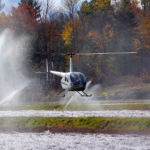 helicopter flying against a background of sprinklers, frozen cranberry vines and fall trees