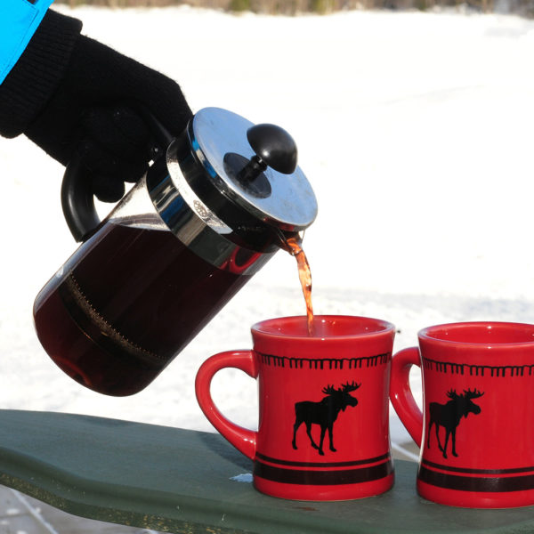 hot mulled wine being poured into two red moose mugs with snow in the background