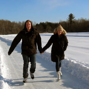 young couple skating the ice trail hand in hand