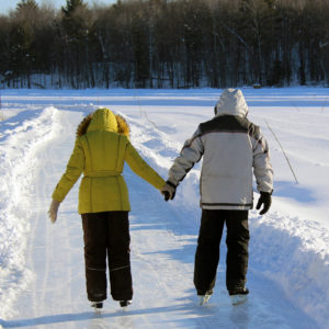 couple skating away on the ice trail holding hands