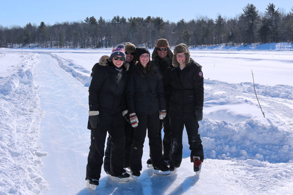 group of five people in skates standing on the ice trail
