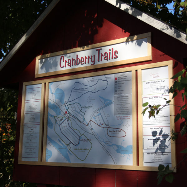 picture of trail head sign at johnston's cranberry marsh with green leaves all around