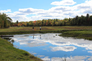 couple hiking along a dike with a blue pond reflecting clouds in the foreground