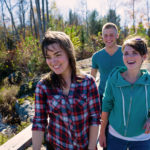 two girls and a guy laughing and crossing a bridge in the woods