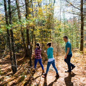 two girls and a guy hiking in the woods in autumn