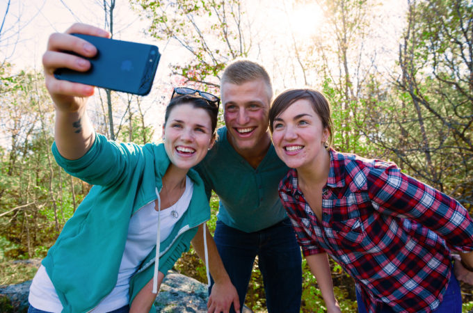 two girls and a guy posing for a selfie in the woods