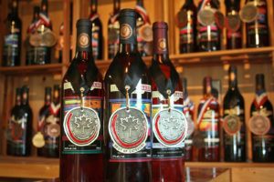 three bottles of Muskoka wine with medals against background of other wines on shelves with medals