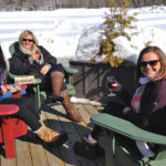 four women in Muskoka chairs enjoying wine on a sunny winter day
