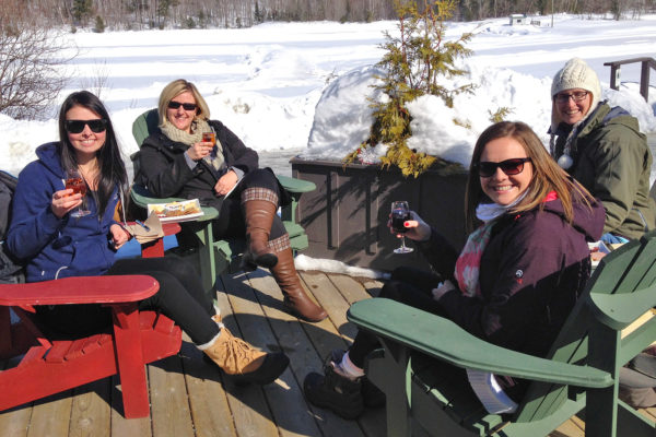 four women in Muskoka chairs enjoying wine on a sunny winter day