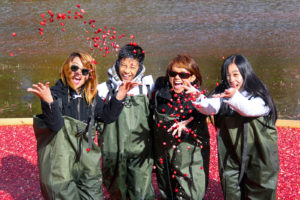 four smiling people tossing cranberries in the air while standing in floating cranberries