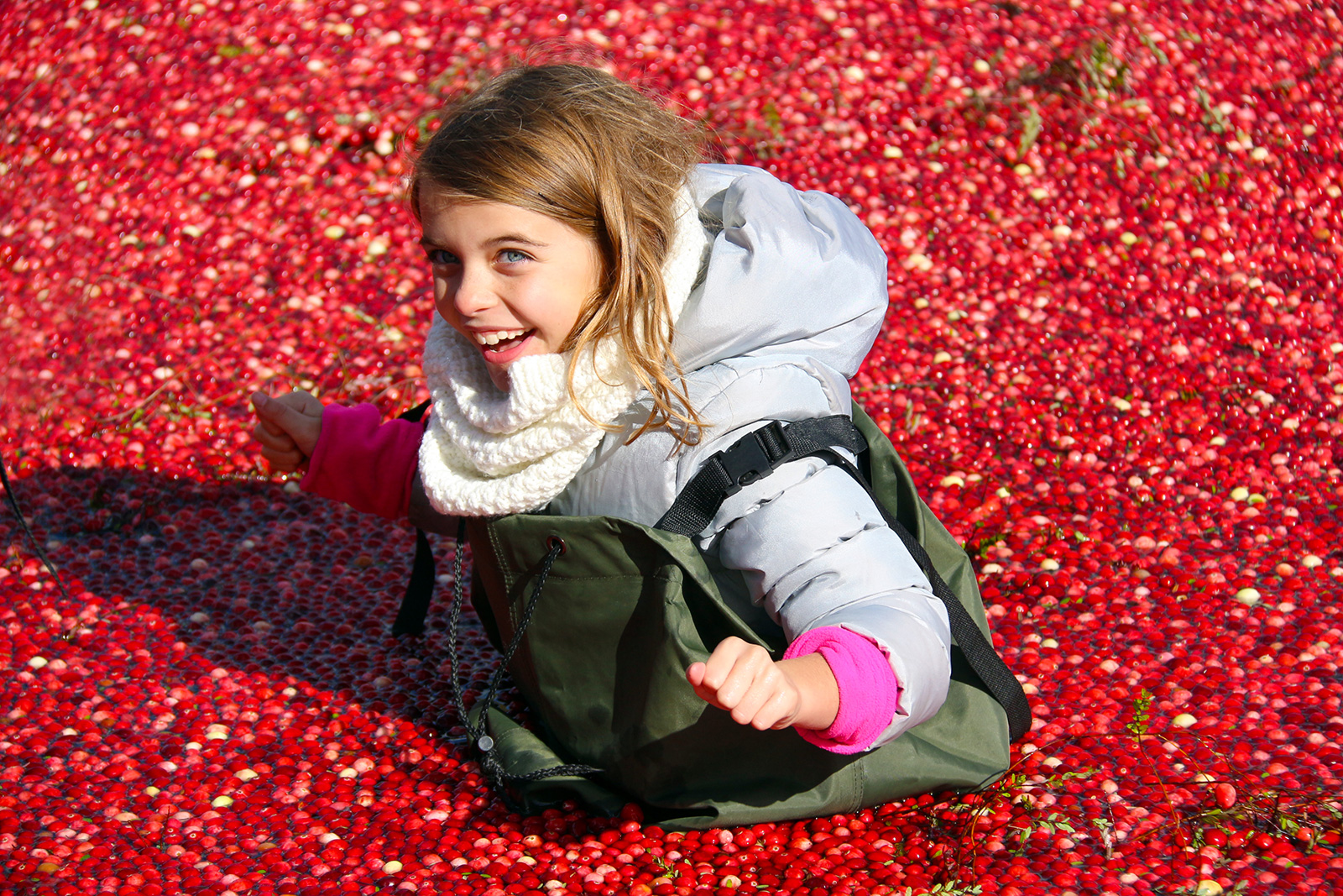 smiling girl standing in floating cranberries