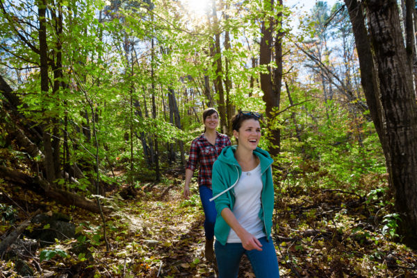 two smiling girls hiking through the woods
