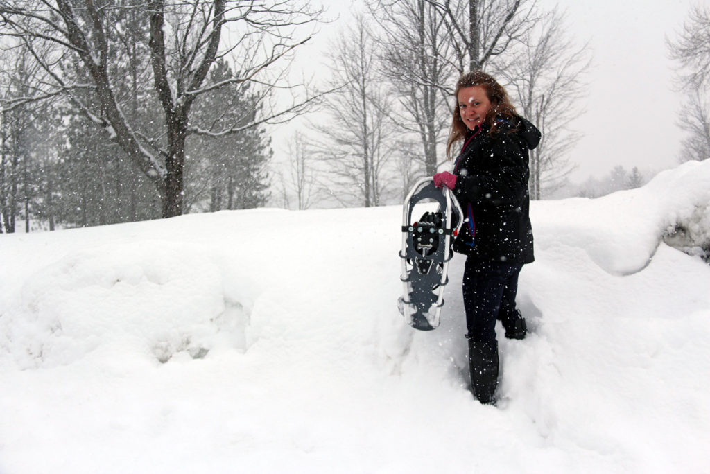woman holding snowshoes with snow falling at Johnston's Cranberry Marsh in Bala, Muskoka, Ontario