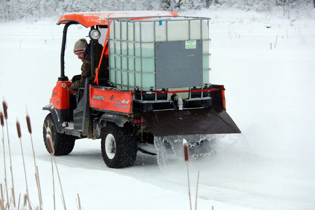 adding water to the ice trail using a kubota rtv and water tote at Johnston's Cranberry Marsh in Bala, Muskoka, Ontario