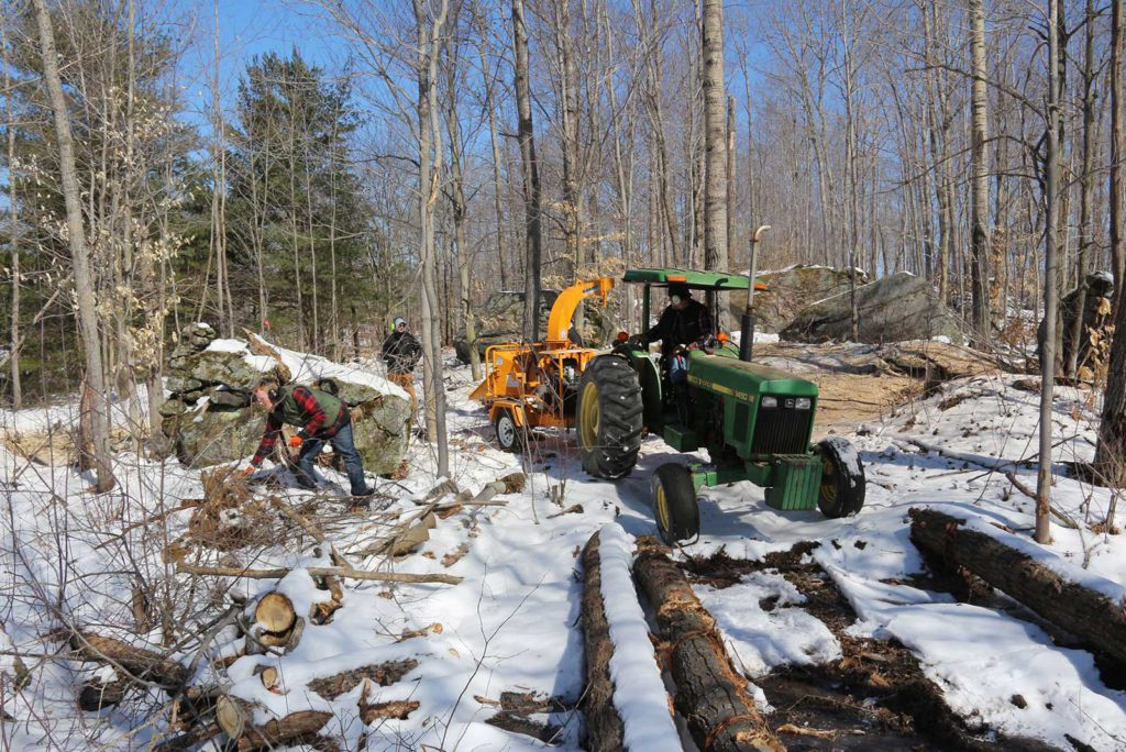 john deere tractor pulling a wood chipper with a crew working on the trails at Johnston's Cranberry Marsh in Bala, Muskoka, Ontario