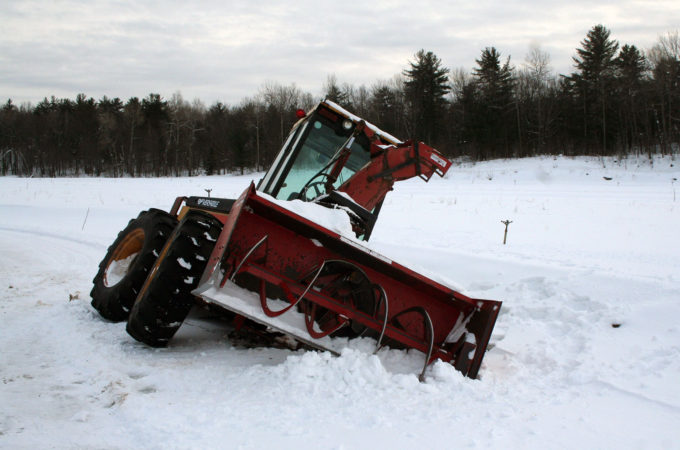 Versatile tractor and snowblower stuck sideways in a ditch
