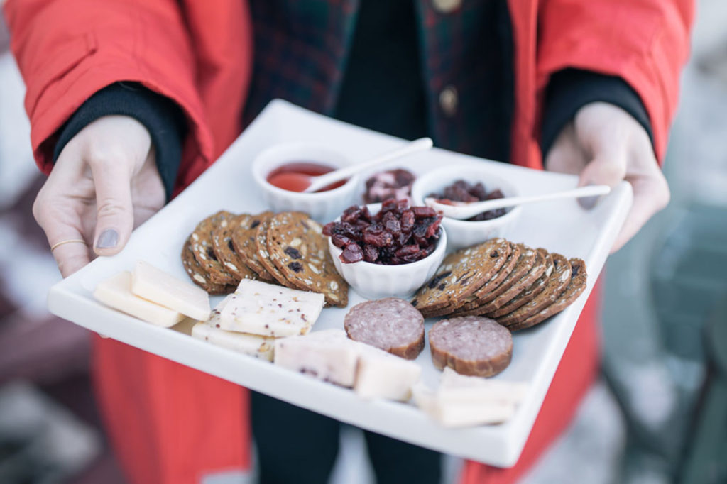 cheese, crackers and preserves on a square, white plate