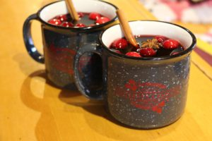 mugs of hot mulled wine with cranberries and a cinnamon stick