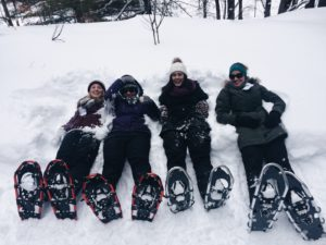 four snowshoers lying in a snowbank